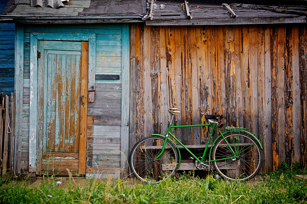 a bicycle parked next to an old wooden shack