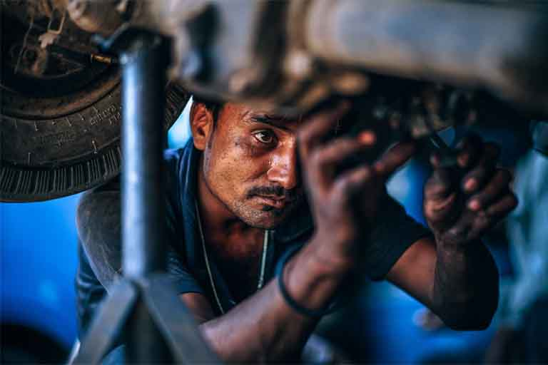 an auto mechanic fixing the engine found in the underbody of the car