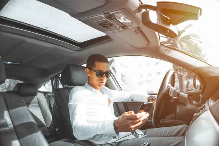a man sitting on the driver's sit while using his android phone