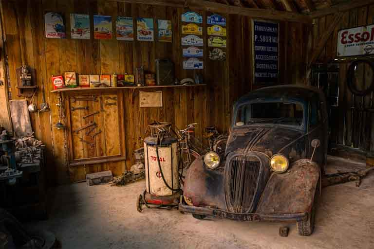 inside the wooden garage with old and rusty vintage car