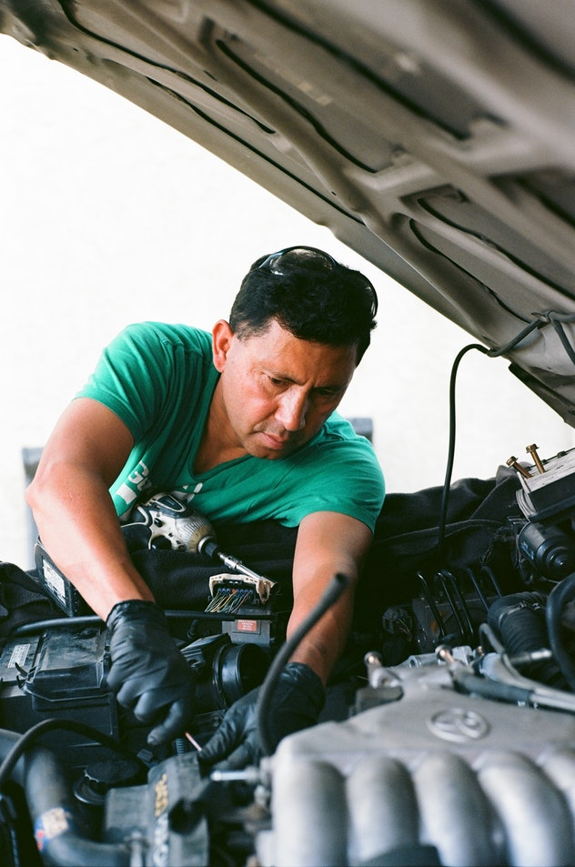 a local auto mechanic working under the hood of the car