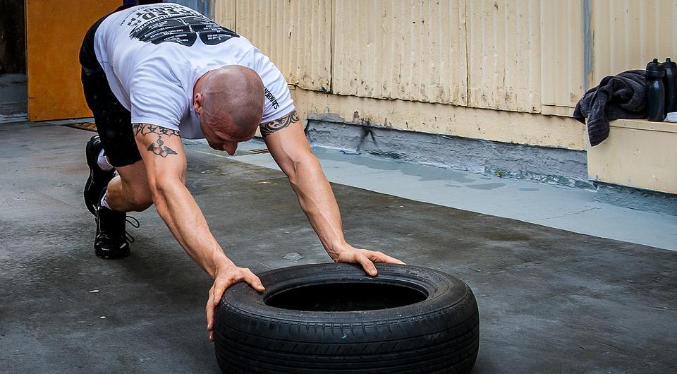 Man pushing tire